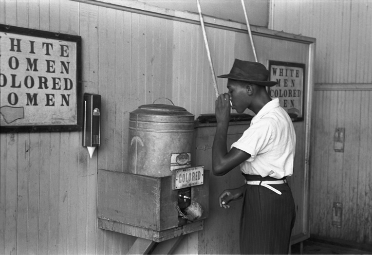 "A young Black man drinking from a ""colored"" water fountain during the Jim Crow era."