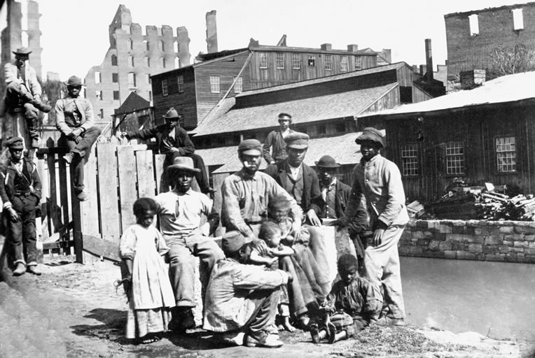 A group of freedmen consisting of Black men, women, and children standing near a canal in Richmond, Virginia during Reconstruction.