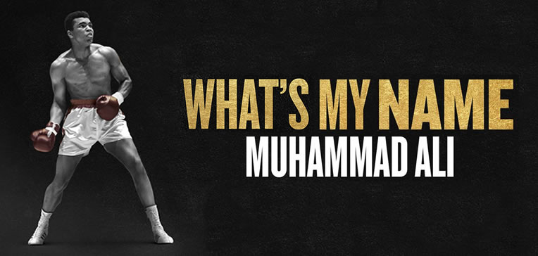 """Muhammad Ali in white trunks with red trim and red gloves in boxer's pose next to gold """"What's My Name"""" title."""