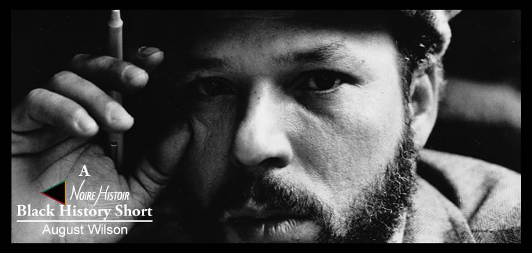 A black and white portrait of August Wilson holding a pen.