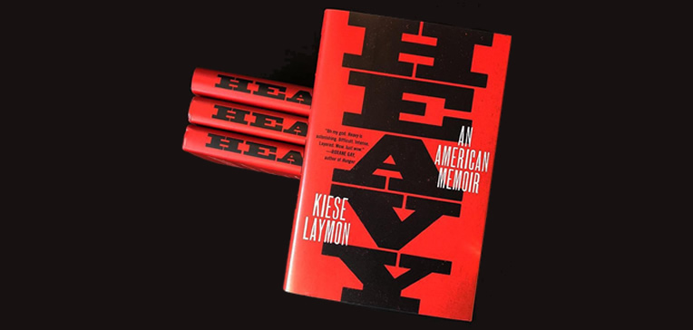 """""""Heavy"""" with the reddish-orange book cover stacked against a dark gray background."""
