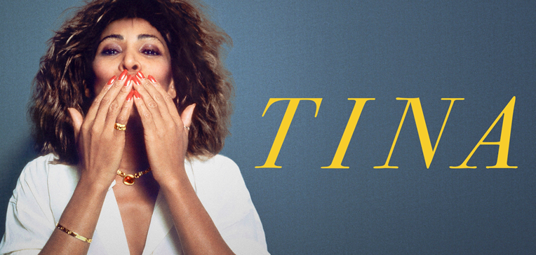 Tina Turner blowing a kiss set against a blue background with her name in yellow.