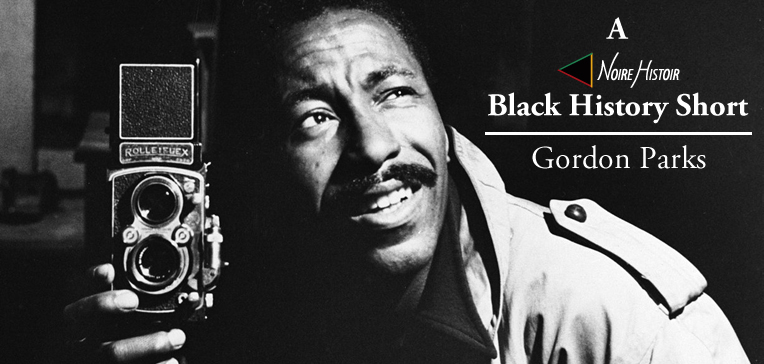 Black and white portrait of a young Gordon Parks holding a camera.